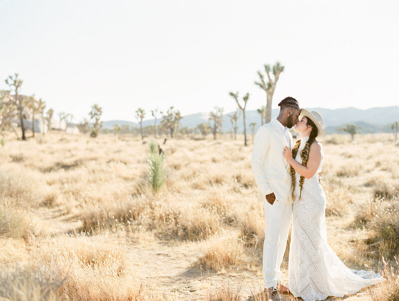 black groom in beige suit kissing his bride in the joshua tree desert