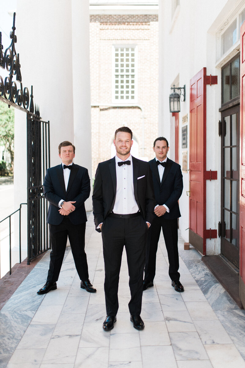 Groom and his groomsmen smile in tuxes outside their wedding venue