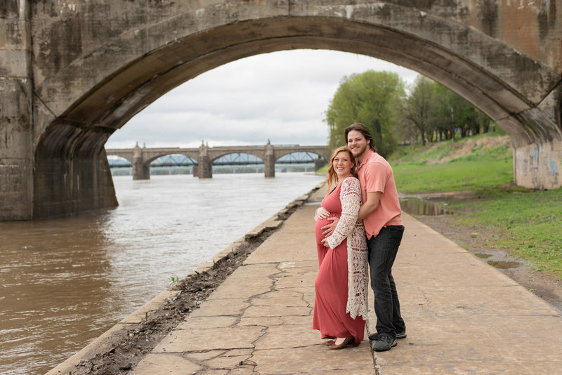 Husband & Pregnant Wife  posed along river with bridges behind them