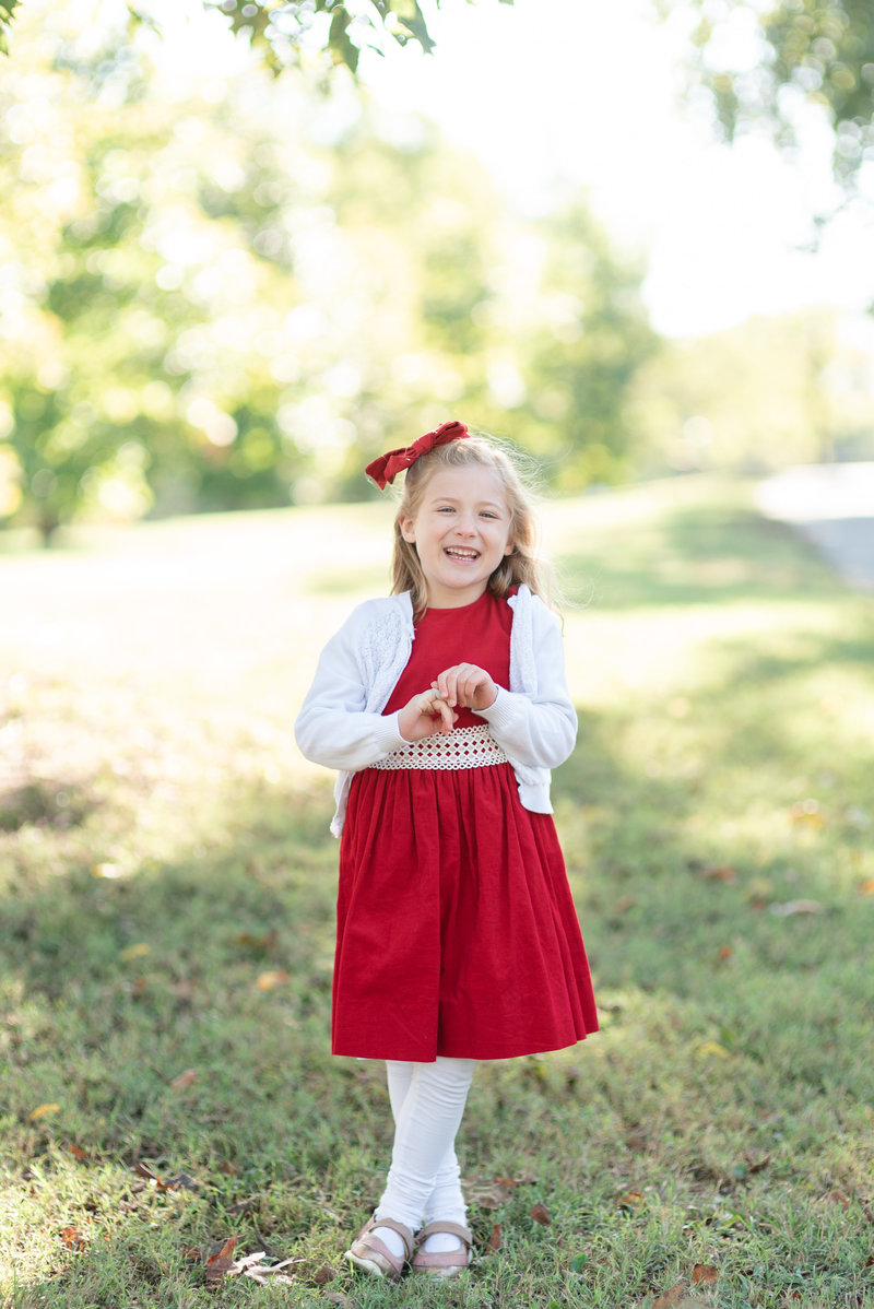 A little girl wearing a red dress is smiling very big for the camera and giggling