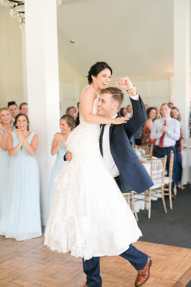 groom carrying bride into reception at springfield manor winery and distillery wedding by costola photography
