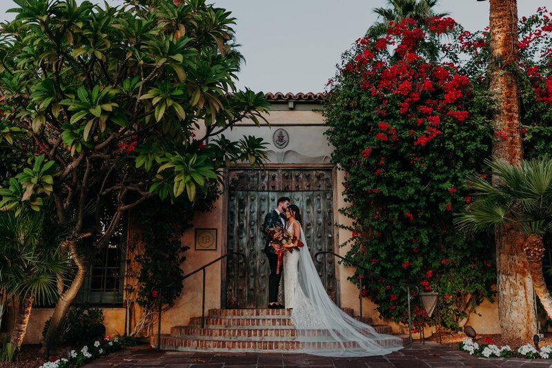 Groom Kisses Bride's Forehead in front of a rustic doorway at the Royal Palms Hotel