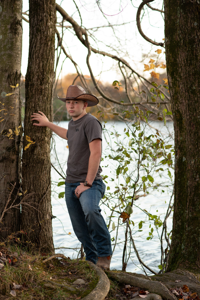 Senior boy in western hat and boots in front of lake