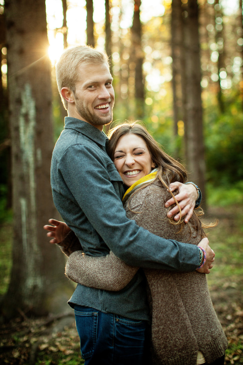 Engaged couple are smiling and hugging in the woods, looking at the photographer with the sun behind them.