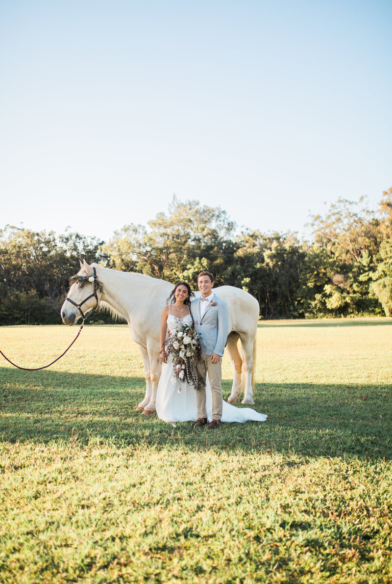 bride and groom  with white horse at sunset ranch hawaii