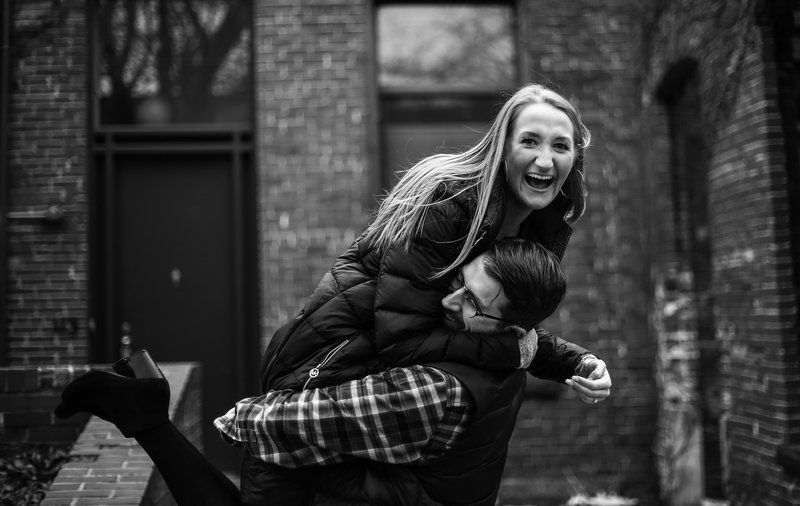 Man picks up fiancee as she laughs during winter engagement photos at Modern Tool Square in Erie, PA