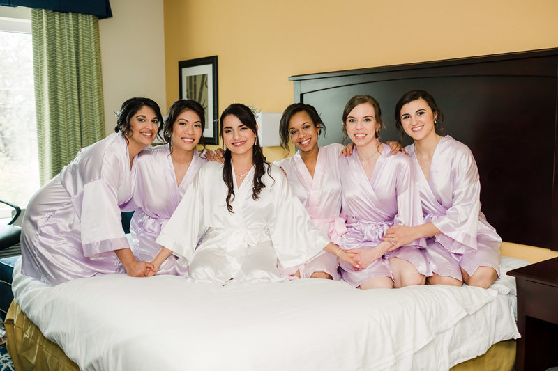 Bride with bridesmaids in robes at hotel near Club Lake Plantation