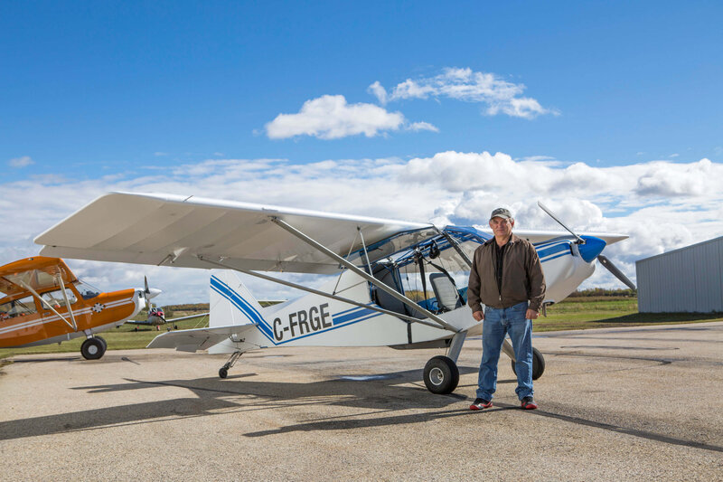 man stands in front of small airplane