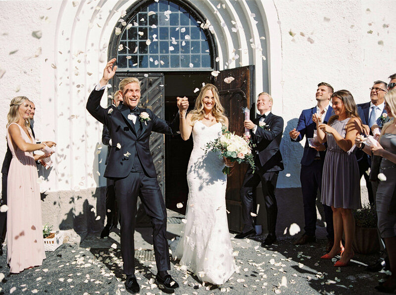 055-bride-and-groom-walking-out-from-the-ceremony-and-white-rose-petals-are-being-tossed