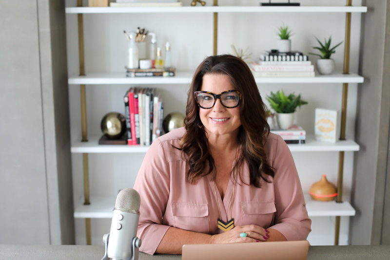 Glossible founder, Sonia Roselli, sits at her desk in beautiful office and smiles in a pink blouse, tortoise shell glasses, and with a podcast microphone