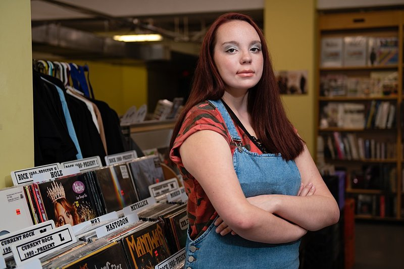 High school senior girl in jean overalls with red camo tee standing with arms crossed against the stacks at Eide's record store in Pittsburgh, PA