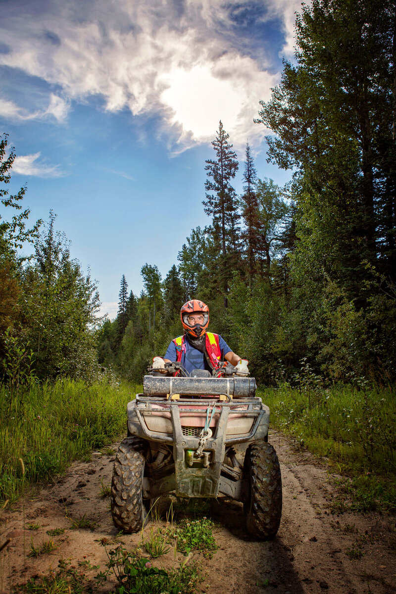 man on a quad with helmet in the forest
