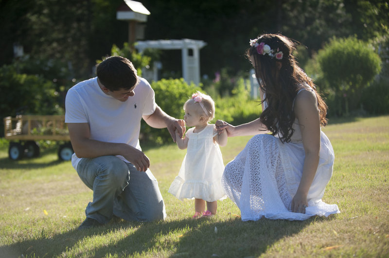 Mother & father hold their toddler's hands outside during family portrait session in Gorham, Maine