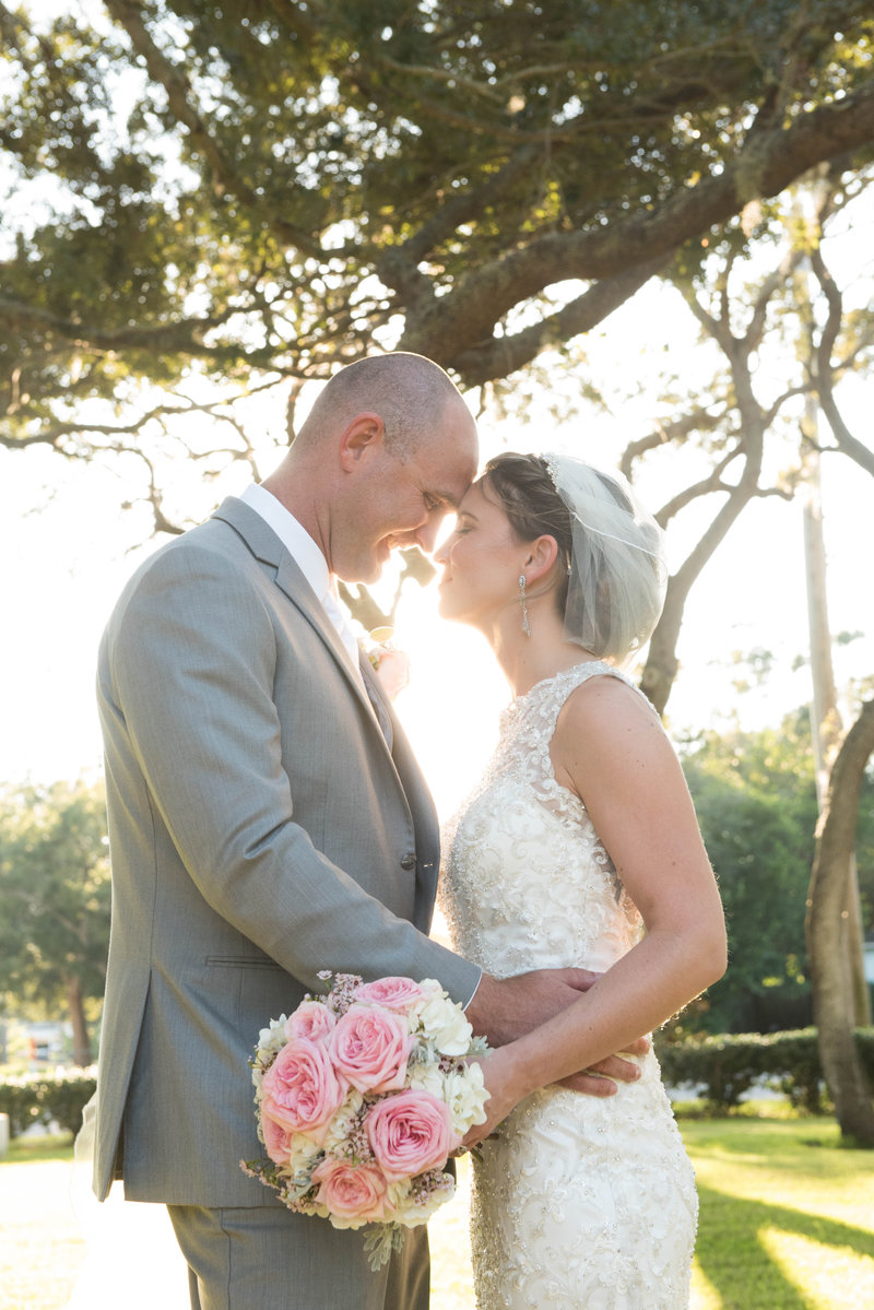 Clearwater Florida wedding couple with foreheads together in the sunlight