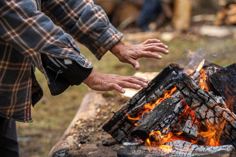 indigenous man warms hands over a fire