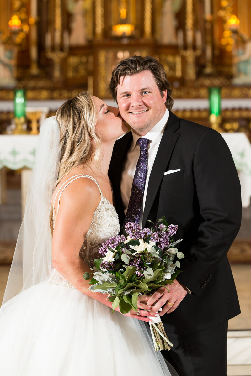 bride kissing groom's cheek at st. john cantius church