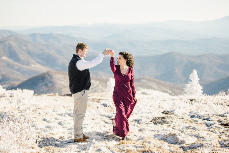 Soon-to-be bride and groom dance together on the top of a mountain during their engagement photos