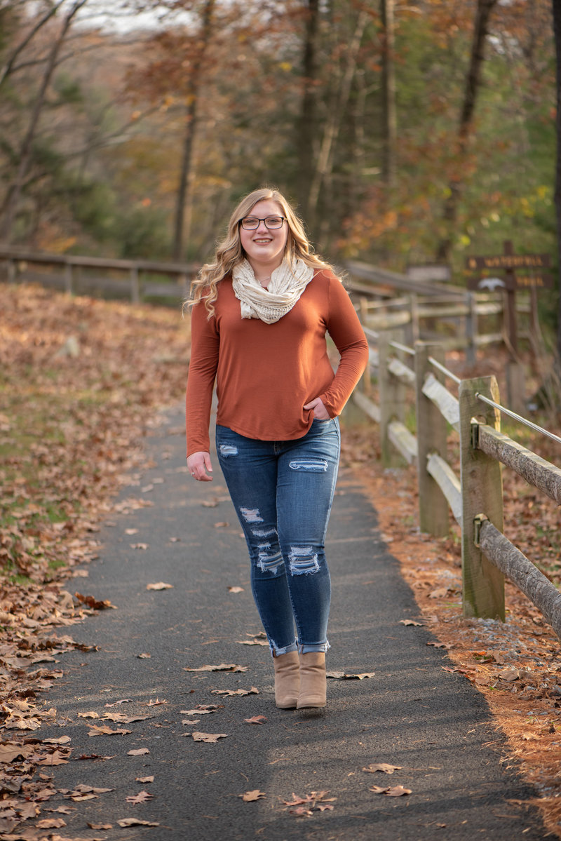 Senior girl in orange top walking on fence-lined path