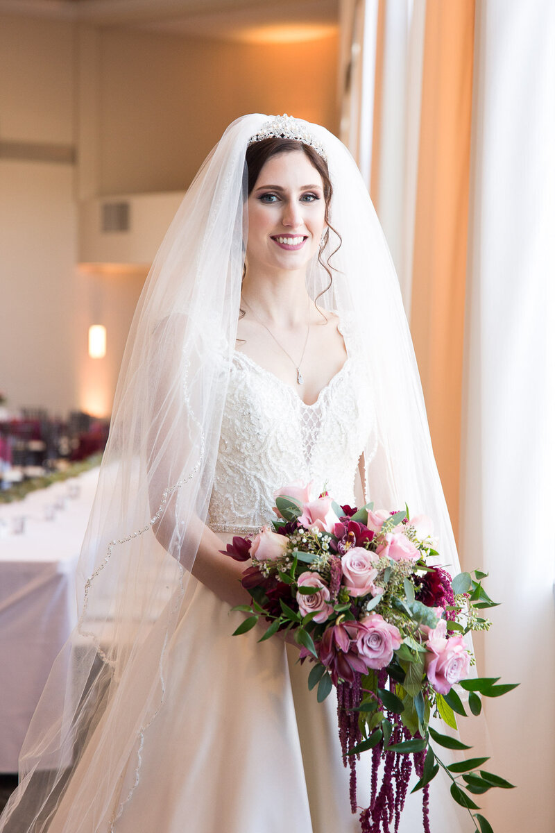 smiling bride with bouquet on wedding day cityflats ballroom port huron