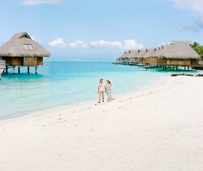 Couple walking on the beach in the conrad Bora Bora with overwater bungalow backside