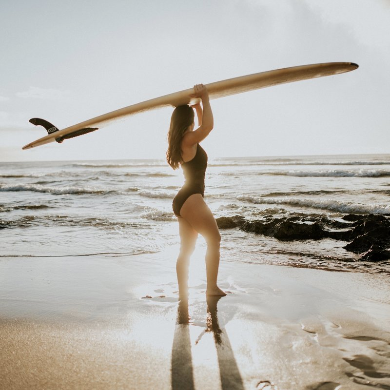 girl carrying surfboard