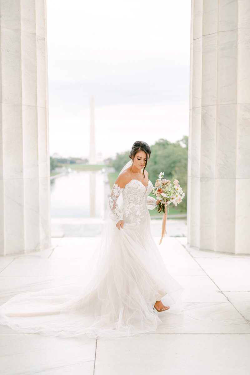 bride fixing dress at Washington DC Romantic Classic Wedding at the Lincoln Memorial by Costola Photography