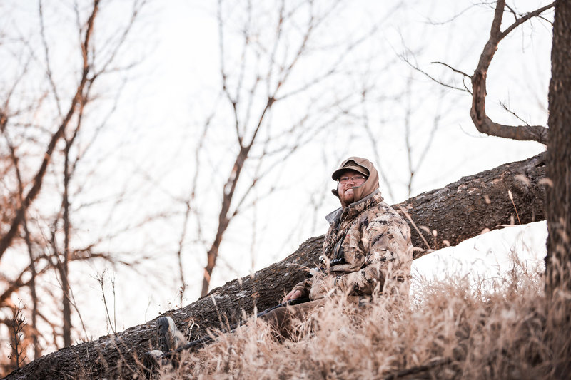 Kansas waterfowl guide sitting in tall grass