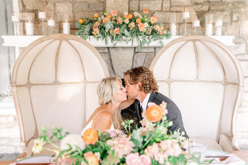 A bride and groom kiss while sitting at their sweetheart table.