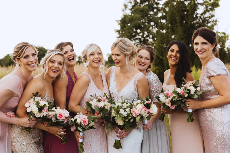 bridesmaids laughing wearing different shades of dresses