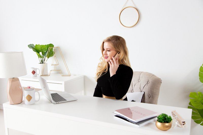 blonde haired women on the phone smiling working on her computer in white home office
