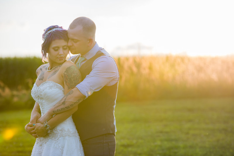 Summer wedding portrait of the bride and groom standing in the field with sunlight