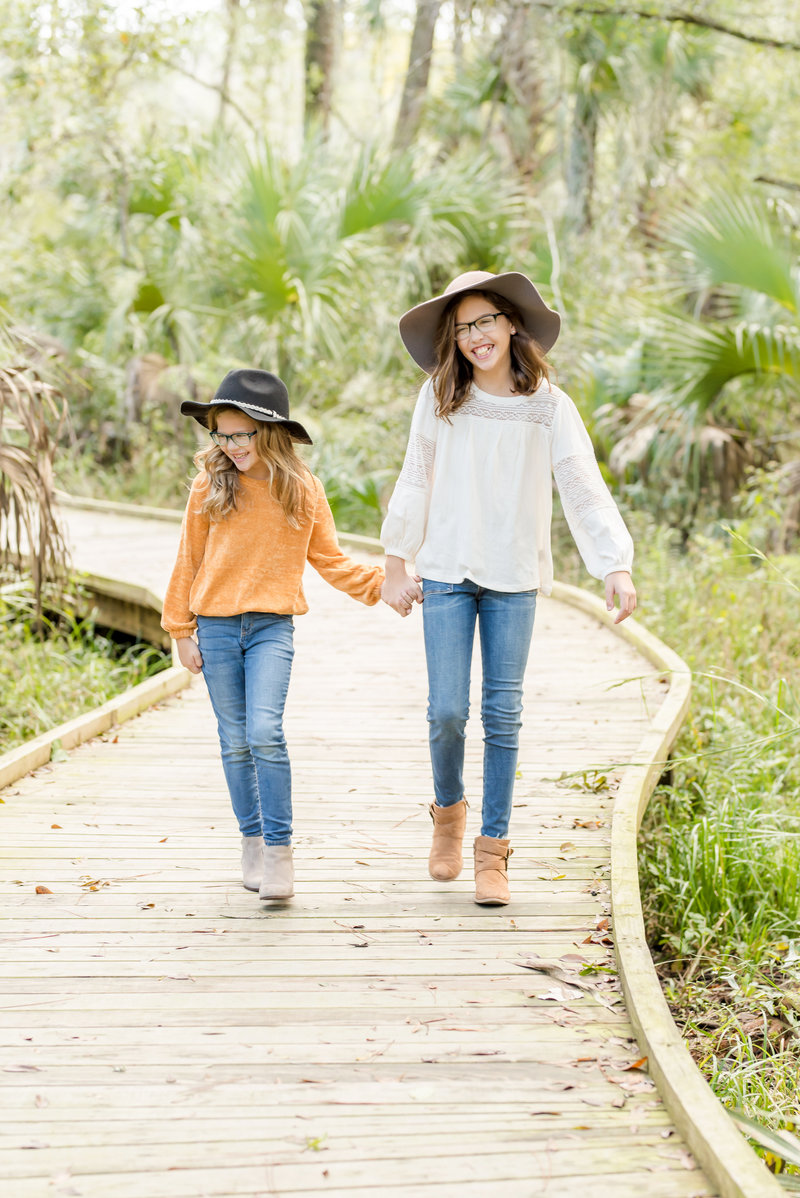 2 young girls in hats hold hands and walk along a path surrounded by palm fronds