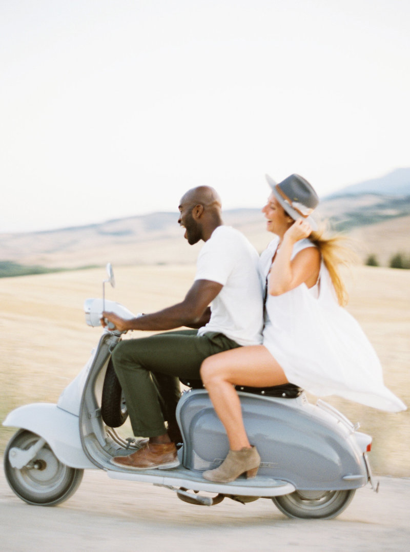 interracial couple riding on a vespa in tuscany