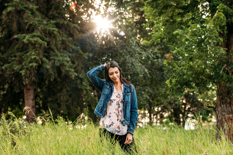 indigenous model in jean jacket  standing in tall grass