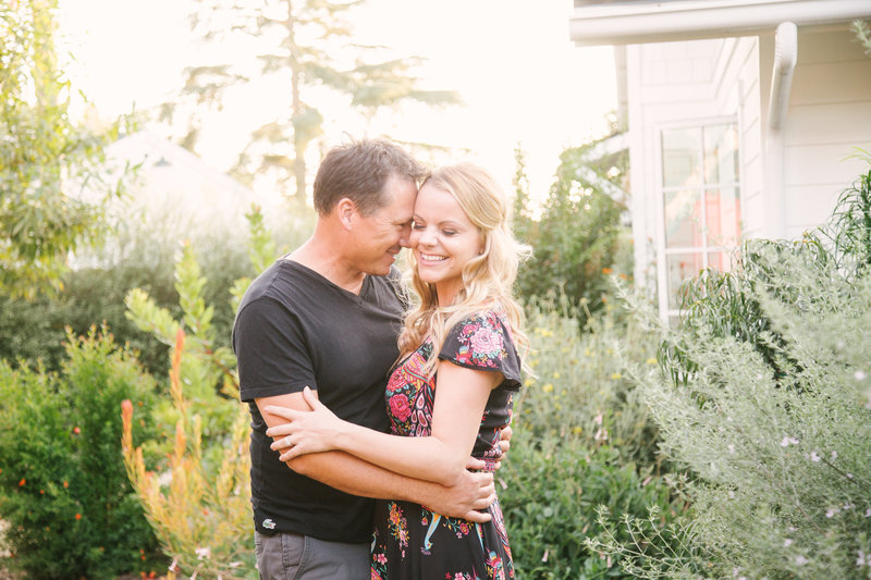 Groom hugs bride during lifestyle Santa Ynez engagement shoot