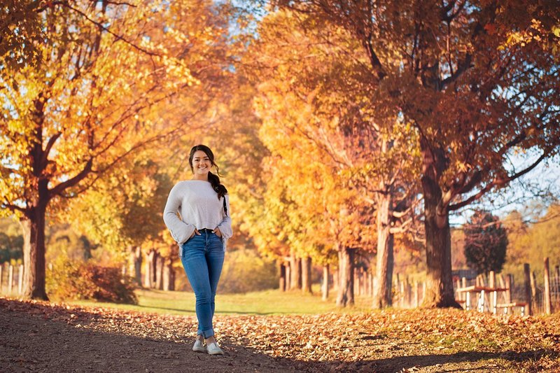 High school senior girl in off-white sweater standing along tree-lined path in the fall when leaves are changing at Round Hill Park in Elizabeth, PA
