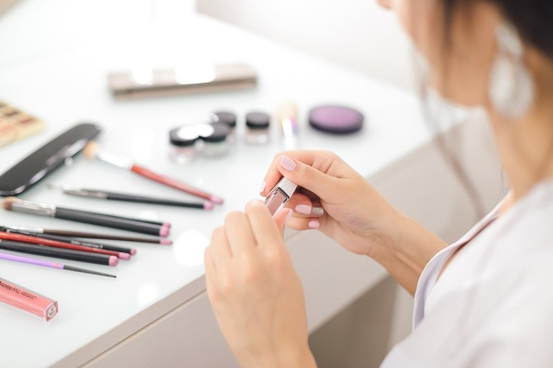 Young woman opens lip gloss while sitting at makeup station