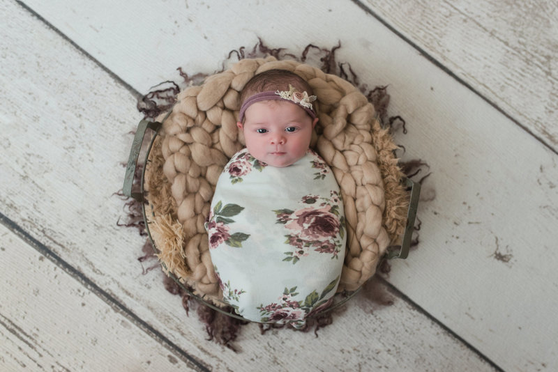 rustic chic floral wrapped newborn baby girl on wood floor