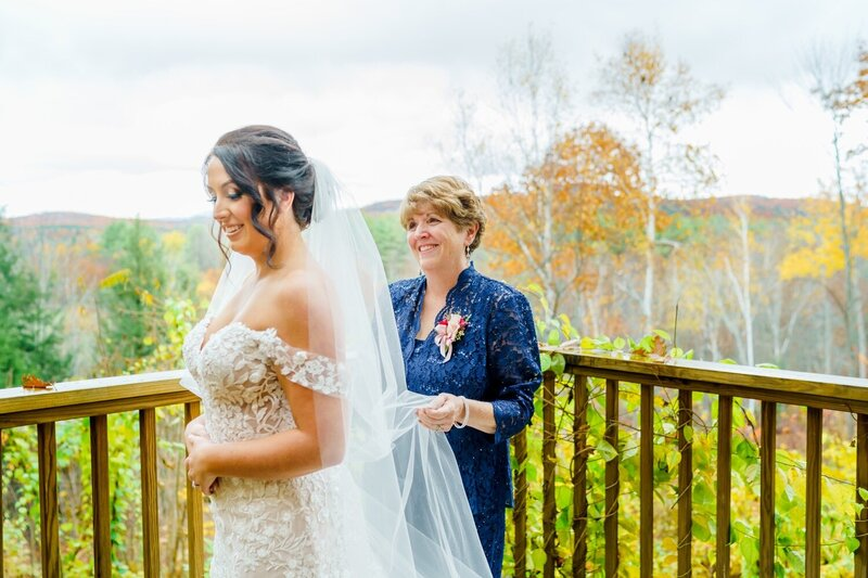 New Hampshire bride and mother of hte bride outside fixing veil