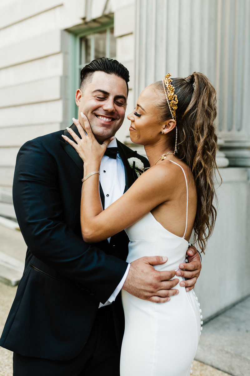 bride touches grooms face as he smiles during their first look at the larz anderson house in washington dc