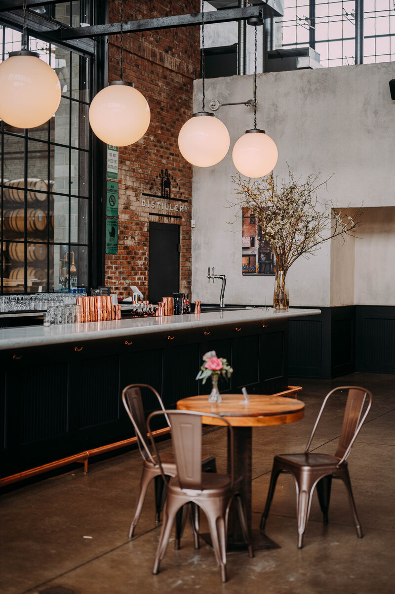 a wooden table sits in front of a marble bar with spherical hanging lights above it in front of a brick wall in philadelphia distilling company shot by philadelphia wedding photographer alex medvick