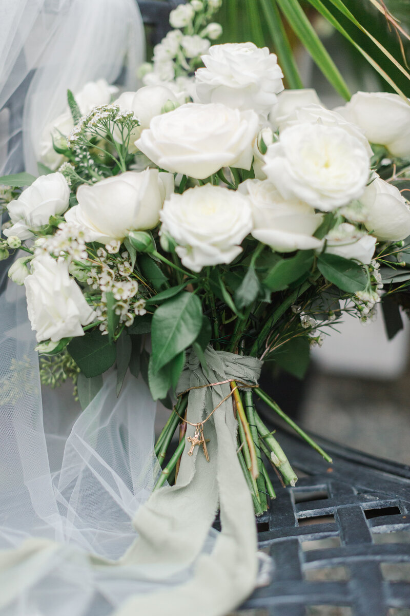 white wedding bouquet with a cross necklace tied to it