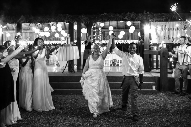 Guests wave sparklers as bride and groom exit Betsy's Barn wedding