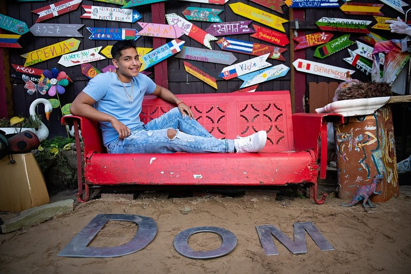 High school senior boy in blue Polo tee seated on red metal couch surrounded by colorful signs and metal letters in sand at Randyland in Pittsburgh, PA