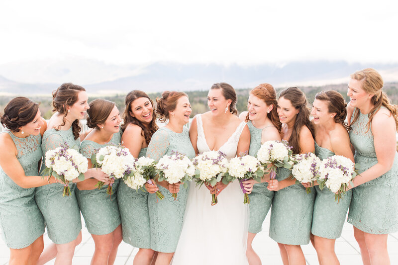 bride and bridesmaids laughing and holding their bouquets