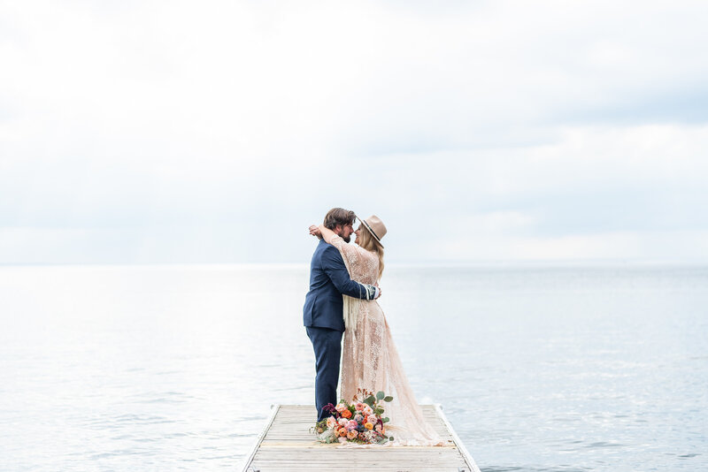 Bohemian bride and groom embrace at the end of a dock on their wedding day