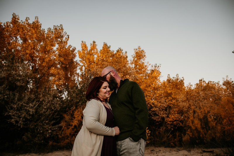 husband kissing wife in front of fall leaves