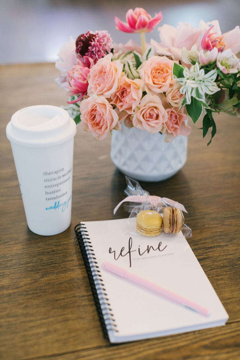 flowers in vase, coffee mug, and notebook on desk