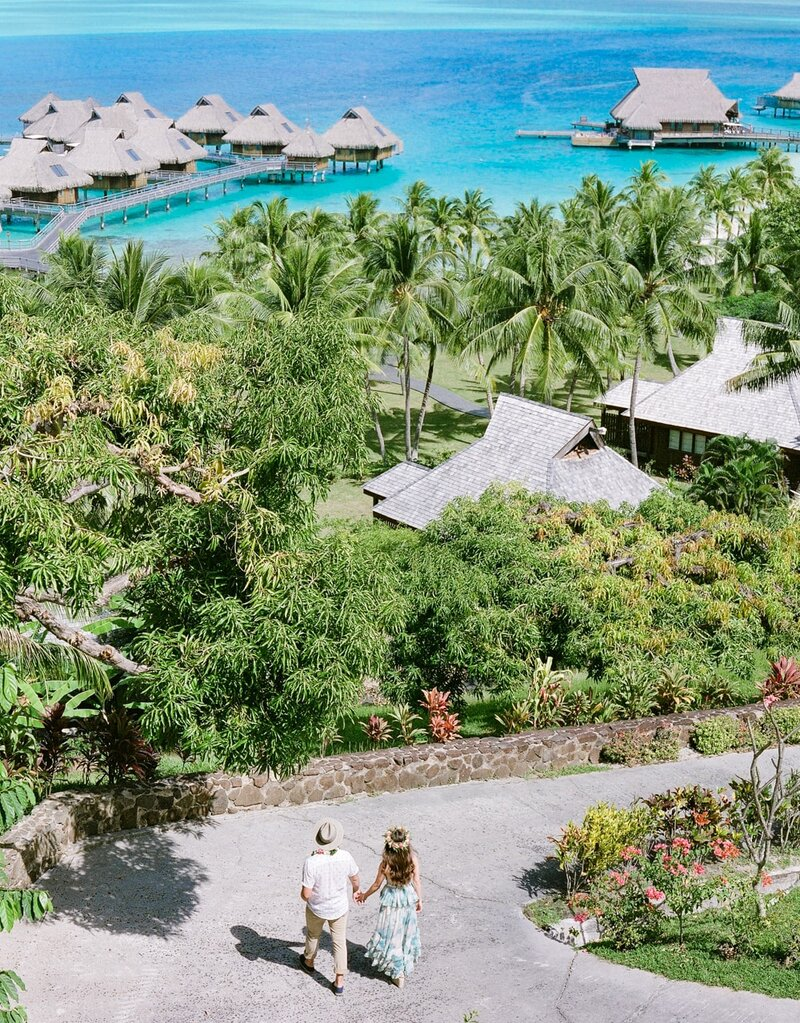 Aerial view on a couple in their overwater bungalow in pacific island