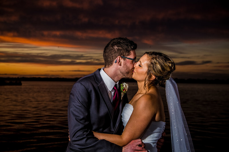 Bride and groom kissing outside Sheraton Erie Bayfront Hotel at sunset